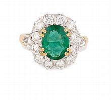 BAGUE en or jaune, ornée d'une émeraude de taille ovale de 2,95 carats dans un entourage de 12 diamants et  épaulée de deux diamants de 1,05 carats. TDD : 55 Poids brut : 8,15 gr  A yellow gold, diamond and emerald ring.
