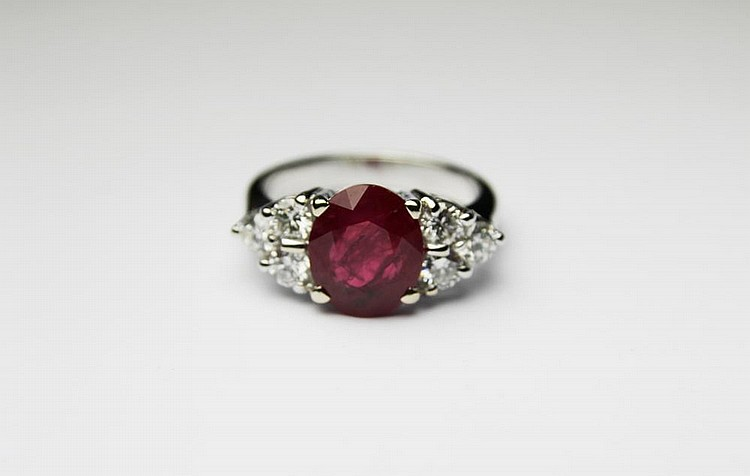 BAGUE en or gris ornée d'un rubis de taille ovale de 3,12 carats épaulé de six diamants de taille brillant. Poids brut : 6,2 g TDD : 52 A RUBY, DIAMOND AND WHITE GOLD RING