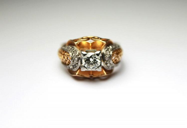 BAGUE en or jaune la monture ajourée et ciselée ornée d'un diamant de taille moderne dans un entourage de diamant de taille rose. Poids brut : 6,1 g TDD : 55 - 54