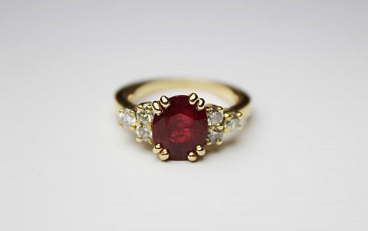 BAGUE en or jaune sertie d'un rubis ovale (env. 2,5 cts) épaulé de trois diamants ronds taille brillant en chute de chaque côté. TDD : 52 (anneau rétrécisseur) Poids brut : 5,8 g.