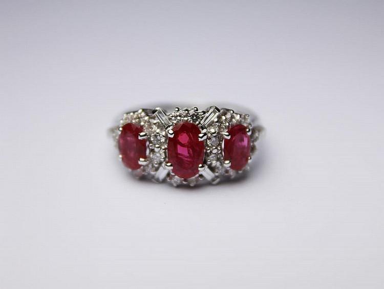 BAGUE en or gris la monture ornée d'une succession de trois rubis de taille ovale dans un entourage de diamants de taille baguette et de taille brilant. Poids brut : 3,9 g TDD : 53 A RUBY, DIAMOND WITH XHITE GOLD RING