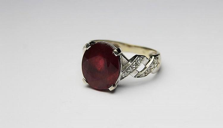 BAGUE en or gris ornée d'un rubis de taille ovale, la montur ajourée et pavée de diamants de taille brillant. Poids brut : 4,1 g