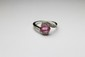 BAGUE en or gris ornée d'un saphir rose de taille ovale entouré de deux volutes pavées de diamants de taille brillant. Poids brut : 4,1 g