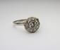 BAGUE en or gris ornée d'un diamant de taille brillant  dans un entourage de diamants de taille brilant. Poids brut : 3,7 g TDD : 55