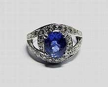 BAGUE TOURBILLON en platine ornée d'un saphir de taille ovale pesant 3,15 carats agrementé de 34 diamants taille brillant pesant 0,90 carat. Poids brut: 10,05 g TDD: 52