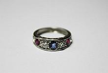 BAGUE en or gris ornée de saphirs et rubis taillés en coussin dans un entourage de diamants de taille ancienne, la monture finement ciselée. Poids brut : 4,7 g TDD : 53