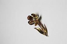 BROCHE en or jaune stylisant une fleur, les pistiles sertis de pierres de couleur et les pétales décorés d'émail orangé. Longueur: 4,5 cm Poids brut: 7,6 g