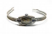MONTRE d'époque Art Déco, le bracelet en or gris, le boitier en platine serti de diamants et de saphirs calibrés.  Poids brut : 20,8 g
