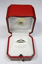 CARTIER BAGUE solitaire, modèle « Louis Cartier », en or gris ajouré serti d'un diamant taille brillant. Chaton en forme de « C » en hommage à Louis Cartier. Signée CARTIER, numérotée et datée 1998. Dans son écrin. Poids brut : 7,7 g.