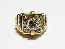BAGUE en or jaune style chevalière sertie de diamants de taille moderne retenant en son centre un diamant monté sur six griffes. Poids brut : 14,7 g TDD : 52