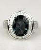 BAGUE en or gris ornée d'un saphir vert de 5,06 carats dans un entourage de diamants de taille baguette.  Poids brut : 8,5 g  TDD : 52