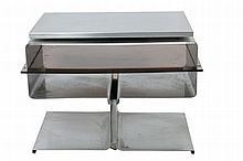 Paul GEOFFROY (XXe) Table basse réalisée en feuilles d'inox pliées et assemblées grâce à une âme en fonte d'aluminium. Dessus tournant sur roulement à billes Editions Uginox Circa 1970 55 x 76 x 45 cm Bibliographie : « Maison française » Numéro 248