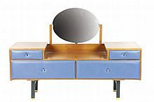 Attribué à Roger LANDAULT (1919-1983) Commode coiffeuse en placage de palissandre, la façade gainée de suédine bleue présente quatre tiroirs, deux ouvrants et deux factices. Le dessus s'ouvre par deux casiers latéraux et est surmonté d'un miroir