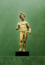 Grèce, Vème siècle avant J.-C.  GUERRIER athénien. Terre cuite. Debout nu.   Pieds et jambe gauche cassés, collés ainsi que la tête et le bras gauche, divers manques.   H. 25,5 cm