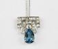COLLIER orné d'une fine chaîne en or gris retenant un pendentif d'époque Art Déco en or gris et platine orné de diamants de taille ancienne et d'une topaze bleu taillée en poire pesant envirion 3 carats. Poids brut : 6,8 g Hauteur : 2,5 cm