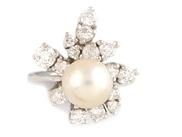 BAGUE en or gris ornée d'une perle blanche réhaussée  par des diamants de taille brillant stylisant un feuillage.    Poids brut: 6,5 g    TDD: 49