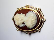CAMEE sur agate deux couches stylisant un portrait de femme de profil dans un entourage d'or jaune ajouré et ponctué de perles probablement fines. Poids brut  16,5 g Hauteur : 4,3 cm Largeur : 3,2 cm