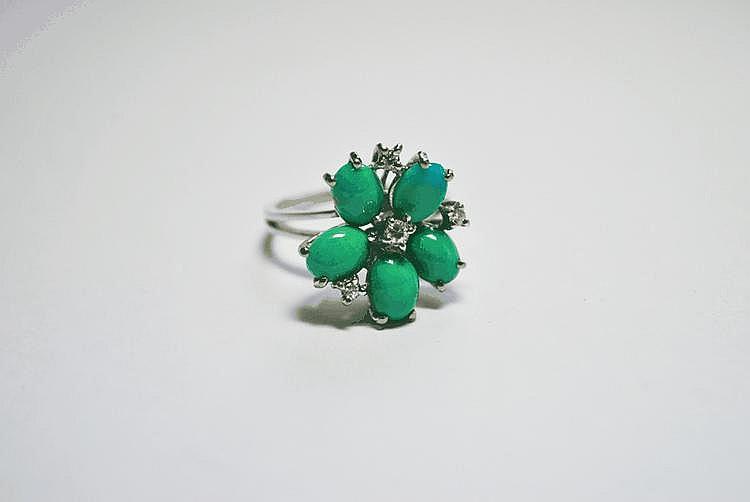 BAGUE en or gris stylisant une fleur ornée de turquoises de taille ovale et ponctuée de diamants de taille brillant.  Poids brut : 5,8 g TDD : 56