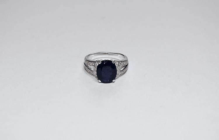 BAGUE en or gris ornée d'un saphir de taille ovale de 3,21 carats, dans un entourage de diamants de taille brillant.  Poids brut : 6,1 g TDD : 51
