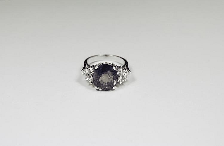 BAGUE en or gris ornée d'un saphir de de Ceylan de taille ovale de 7,08 carats dans un entourage de six diamants de taille brillant.  Avec son certificat AIGS attestant sans modification thermique.  Poids brut : 7,1 g TDD : 52