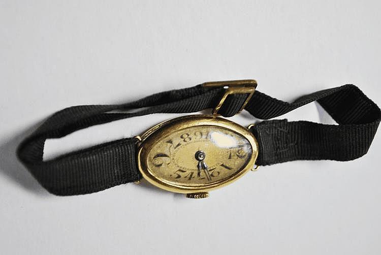 MONTRE en or jaune, le bracelet en tissu noir.  Poids brut : 10,6 g