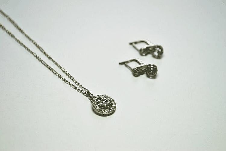 DEMI-PARURE en or gris composée d'un pendentif et sa chaine, la monture ajourée et pavée de diamants retanant en son centre un diamant de taille brillant, la monture ajourée, et une paire de boucles d'oreilles en chute ornée de deux diamants de