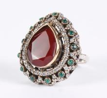 MOGHUL STYLE RUBY RING - A pear cut red ruby is bezel set in golden bronzed silver, and outlined in clear topaz above a sterling lat...