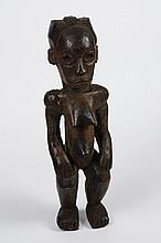 CARVED WOOD FANG FIGURE - From Gabon, Cameroon and Equatorial Guinea. Standing female figure of solid proportion with bent legs, han...