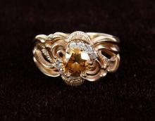 LADY'S CHAMPAGNE DIAMOND RING - The 14 kt yellow-gold mounting features a triple-split shaft extending up the shoulders to a central..