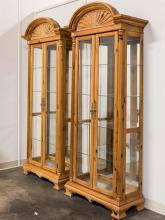 PULASKI: PAIR OF DISPLAY CABINETS - Traditional design pine and pine veneers; each with large shell design crest, multi-paned double...