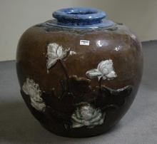 LARGE CERAMIC DECORATIVE POT - Round form; decorated with lotus flowers in relief; brown, blue and white glazes. Apparently unmarked...