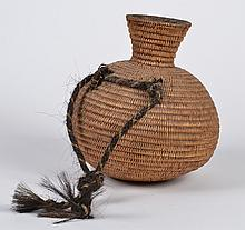 PAIUTE WATER JUG - Willow, with pitch interior. Attached are two loops of coiled horsehair, which hold a horsehair rope of alternati...