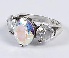 SILVER MYSTIC TOPAZ LADY'S RING - A 7.00 ctw oval mystic topaz, flanked by two round faceted clear gems, white sapphires or white to..