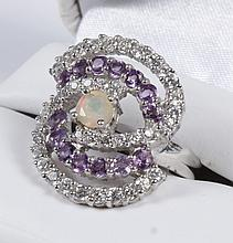 AMETHYST AND OPAL RING - Sterling silver mounting with a central round iridescent pink-white opal, encircled with swirls of bead set...