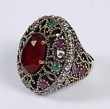 DOME RING WITH RUBY - The large oval ruby is set within an intricate gold embellished lattice set with alternating round rubies and...