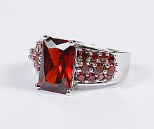 GARNET RING - A large cushion cut rectangular garnet is prong set in a sterling silver mounting, stamped