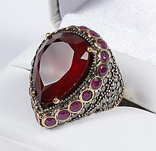 GARNET, RUBY AND SAPPHIRE DOME RING - A large pear-shape faceted garnet (21mm x 17mm maximum) is in a gold-embellished setting above...