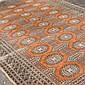 HAND KNOTTED PAKISTANI BOKHARA - Wool on cotton warp, red field, 3 rows of multiple geometric medallions, regimental geometric desig...