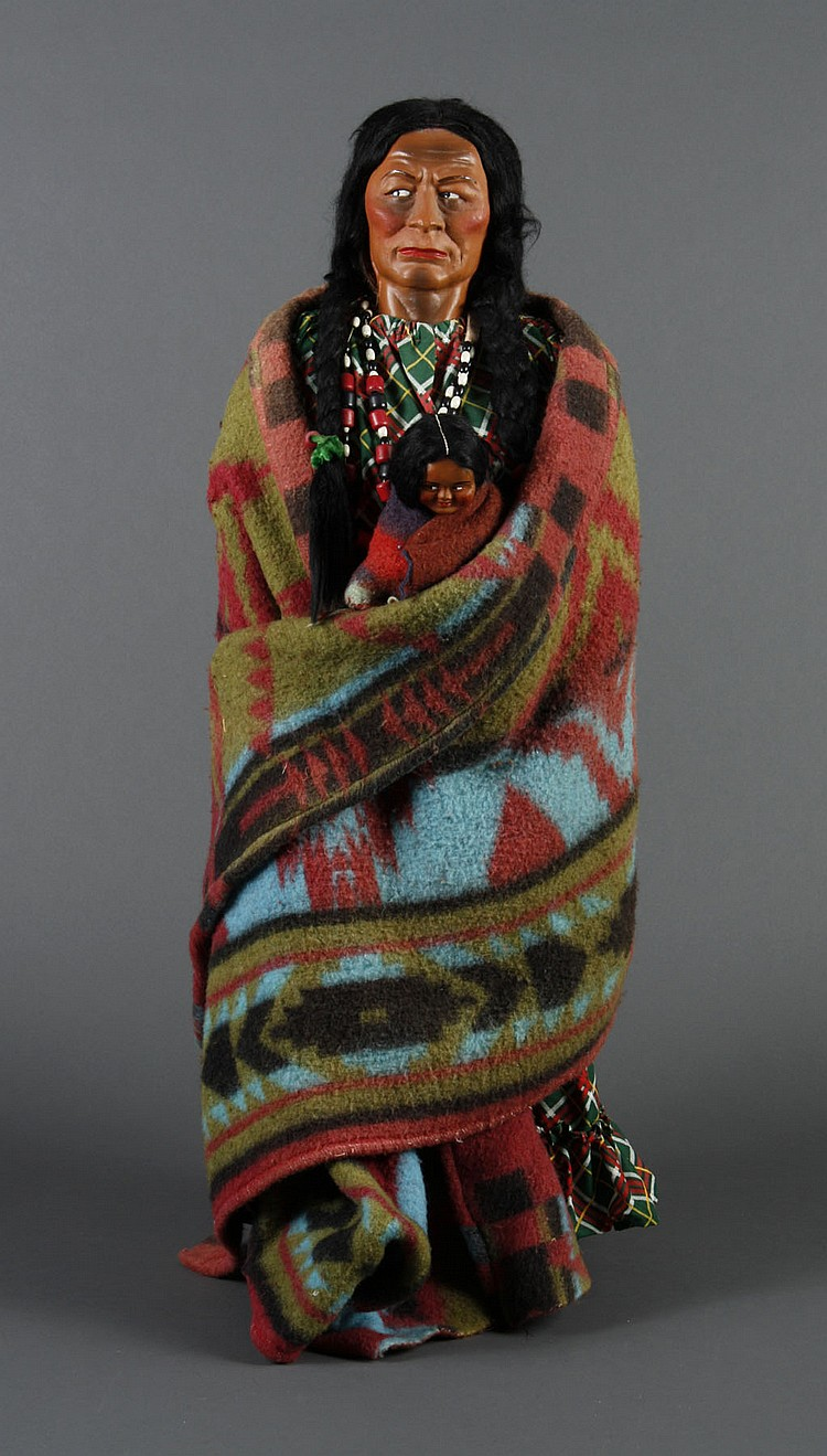 "32"" SKOOKUM DOLL TRADING POST DISPLAY - Native American female Skookum doll holding a papoose; both wrapped in a colorful blanket"