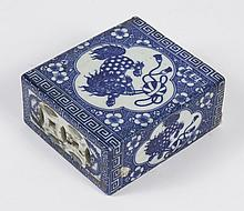 CHINESE BLUE/WHITE OPIUM PILLOW - Openwork coin motifs at one end, between a pair of fu bat motifs. Each side shows a fu dog at play...