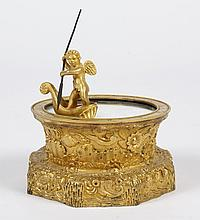 SMALL BRONZE TABLE CLOCK - Cast gilt bronze with circular case and octagonal base chased with scrolls, waves and flowers. Time indic...