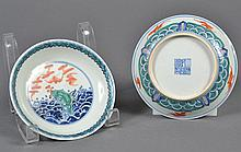 PAIR CHINESE PORCELAIN DOUCAI SAUCERS - In traditional contrasting and joined colors shows blue waves, a green rock sprouting red fu...