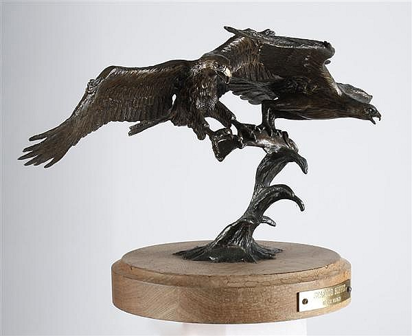 CARL WAGNER BRONZE SCULPTURE ON WOOD BASE - Signed and dated ('83) sculpture of two eagles with a salmon in their talons, perched on..