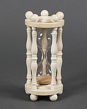 ASSEMBLED CARVED IVORY HOUR-GLASS - Rests on five round feet; turned columns encircle the hour-glass and terminate in five round fin...