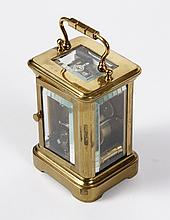 SUB-MINIATURE CARRIAGE CLOCK WITH LEATHER TRAVELLING CASE - Brass clock case with 4 original beveled glass panels; white porcelain fr..