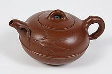 CHINESE YIXING CLAY TEAPOT - Reddish brown with a bamboo modeled handle and leaf sprig. Character seal to base. Condition good. 4