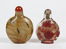 TWO CHINESE SNUFF BOTTLES - Comprising one carved agate bottle in shades of caramel and white with carnelian cap and bone spoon; the...