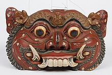 BALINESE CARVED WOOD TEMPLE BELL - In the folk art style, portraying a red and black demon with bulging eyes and bared fangs; having...