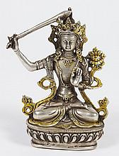 TIBETAN SILVERED AND GILT METAL FIGURE OF JAMPELYANG - Raising a sword of discriminating wisdom in his right hand; the left hand rai...