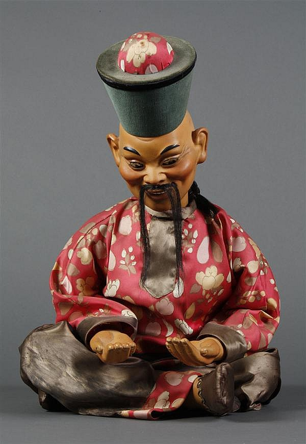 CHINESE ADVERTISING FIGURE - Seated composite Chinese electric nodder figure of a seated man with extended hands in cloth costume. A...